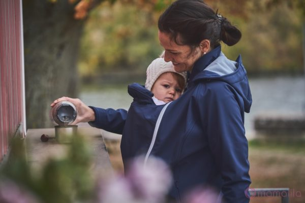 Frau trägt ihr Baby vor dem Bauch unter einer wasserdichten Tragejacke