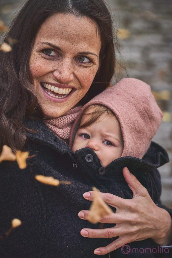 Frau trägt ihr Baby vor dem Bauch unter einer Tragejacke aus Filz von Mamalila