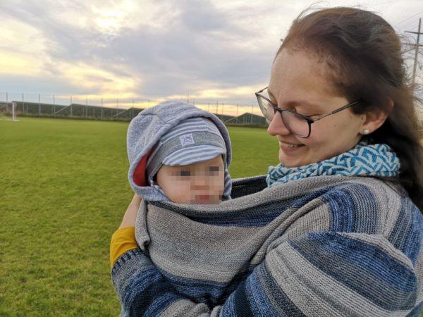 Frau mit Baby in einer Trage oder einem Tragetuch vor dem Bauch unter einem warmen Pulli