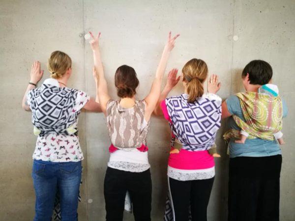 Vier Frauen mit Tragepuppen im Tragetuch auf dem Rücken