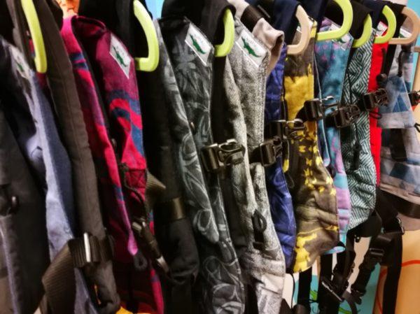 Viele Fullbucke Tragehilfen hängen auf Kleiderbügeln