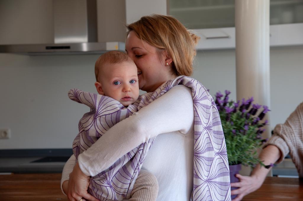Eine Mutter bindet ihr Baby ins Tragetuch ein