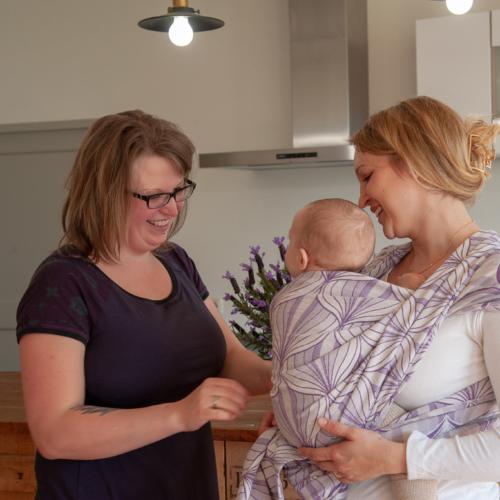 Trageberaterin hilft Mutter mit Baby beim Tragetuchbinden