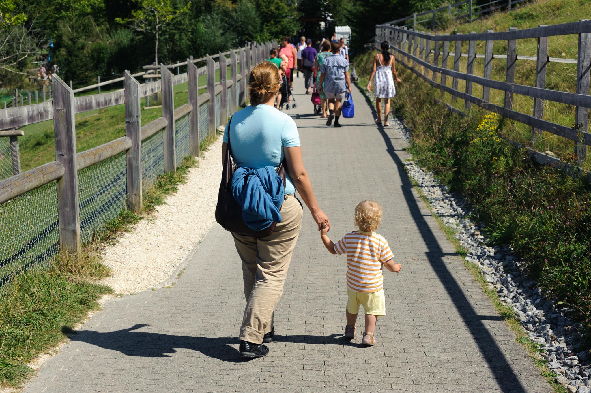 Frau und Kind spazieren Hand in Hand, aus der Handtasche guckt ein Tragetuch heraus
