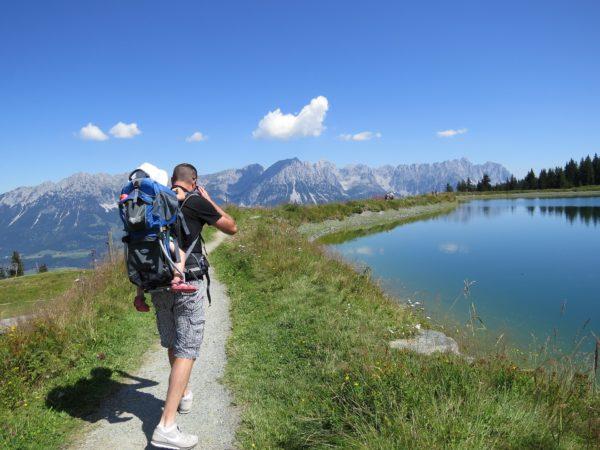 Mann mit Kind in Kraxe vor Bergpanorama